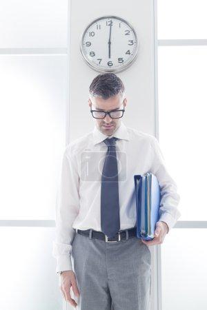 homme d'affaires debout sous une horloge