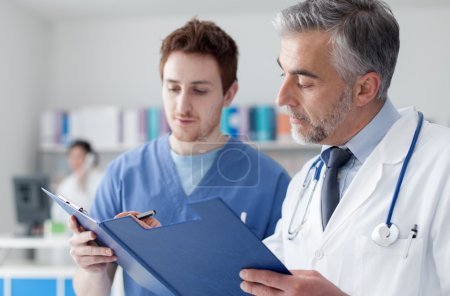 Doctor and practitioner examining records