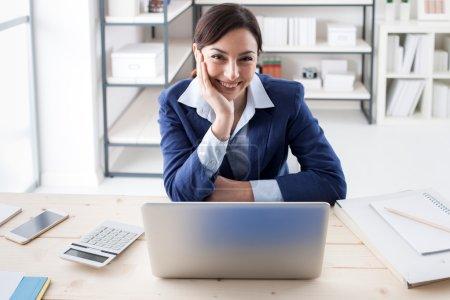 Photo pour Femme exécutive souriante confiante posant dans son bureau avec la main sur le menton - image libre de droit