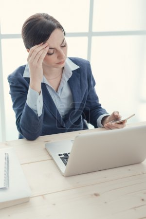 Pensive businesswoman reading sms
