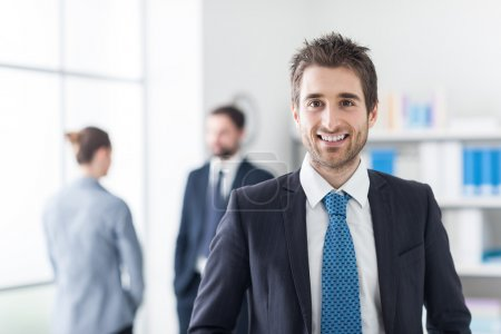 Photo for Confident young executive posing in his office, business team in the background - Royalty Free Image