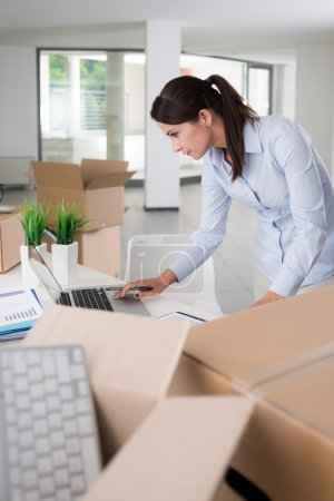 Photo for Young businesswoman using a laptop and unpacking carton boxes in her new office, new business concept - Royalty Free Image