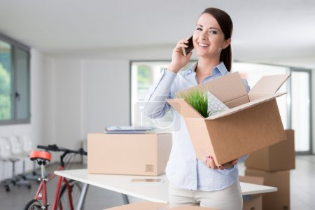 Photo for Beautiful smiling woman moving in a new office, talking on the phone and holding an open cardboard box - Royalty Free Image