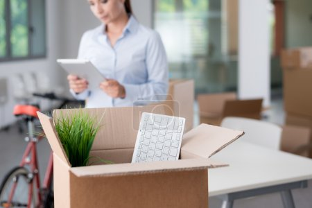 Photo pour Femme d'affaires se déplaçant dans un nouveau bureau, qu'elle utilise une tablette numérique, la mise au point sélective, ouvrir la boîte en carton sur le premier plan - image libre de droit