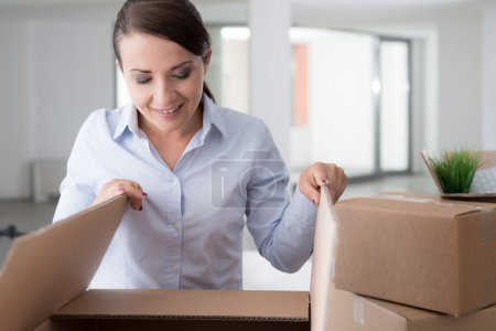 Photo for Happy curious woman unpacking and moving into her new office, she is opening a cardboard box and looking into it - Royalty Free Image