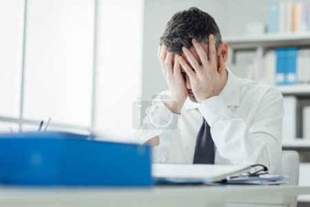 Photo for Stressed exhausted man working at office desk with head in hands, he is overloaded with paperwork, stressful job concept - Royalty Free Image