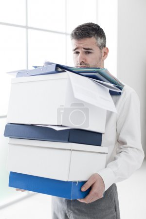sad businessman carrying a load of boxes