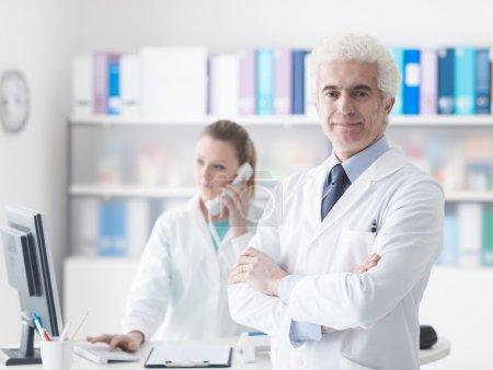 Foto de Profesional médico con su joven asistente en la oficina, ella está contestando llamadas telefónicas, él está sonriendo a cámara - Imagen libre de derechos