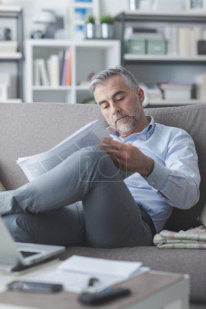 Photo pour Homme d'affaires confiant lisant un journal à la maison, il est assis sur le canapé et relaxant - image libre de droit