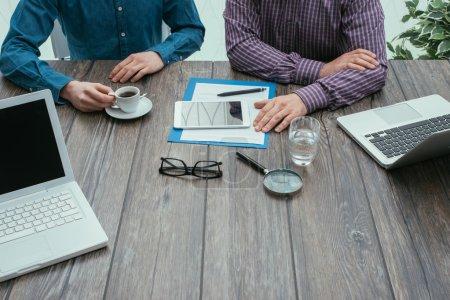 businessmen are working together at desk