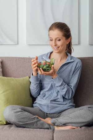 Young woman having lunch at home