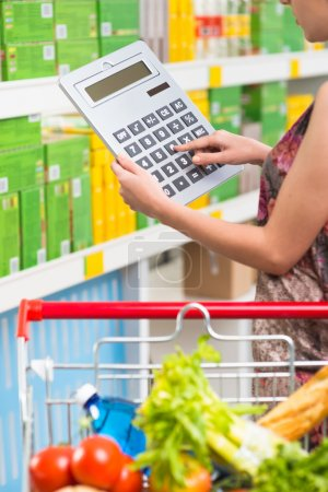 Photo for Woman shopping at supermarket with shopping cart and big calculator checking prices. - Royalty Free Image