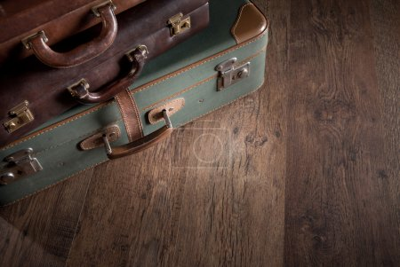 Vintage luggage close-up on dark hardwood floor, t...