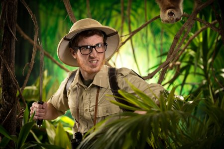 Photo pour Explorateur agressif et confiant marchant dans la jungle tenant une machette avec un animal féroce en arrière-plan . - image libre de droit