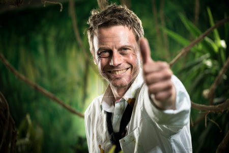 Photo pour Homme d'affaires gagnant avec succès dans les vêtements déchiré souriant avec les pouces levés - image libre de droit