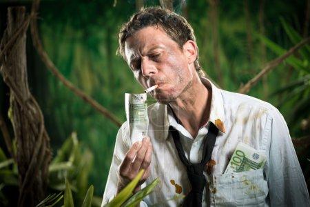 Photo pour Homme d'affaires perdu dans la jungle allumant une cigarette avec un billet de banque . - image libre de droit