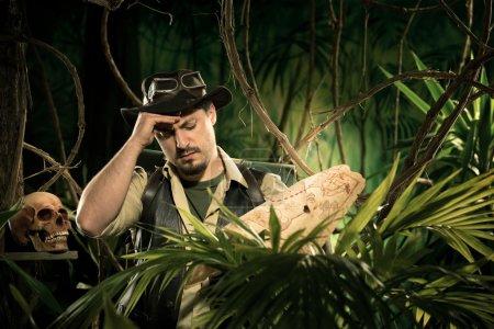 Photo pour Jeune explorateur perdu dans la jungle examinant une vieille carte . - image libre de droit