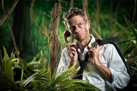 Photo pour Homme d'affaires déprimé en vêtements déchirés perdu dans la jungle ayant un appel téléphonique . - image libre de droit