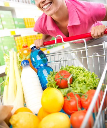 Photo for Young woman in pink shirt leaning to a shopping cart at supermarket. - Royalty Free Image