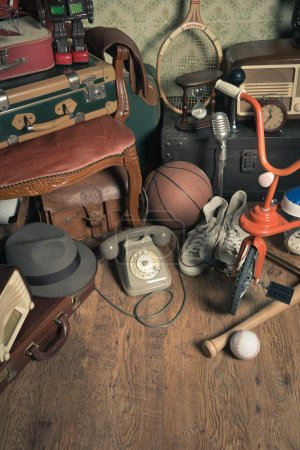 Photo for Group of vintage assorted items on attic hardwood floor with vintage wallpaper background. - Royalty Free Image