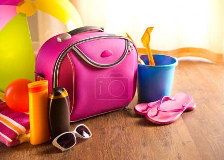 Photo for Summer holidays background with pink bag, sun cream, flip flops and beach toys. - Royalty Free Image