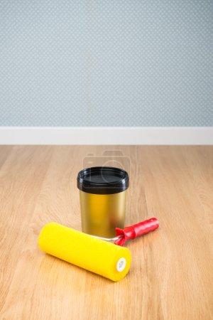 Photo pour Rouleau de peinture et seau de couleur sur plancher de bois franc prêt pour la peinture . - image libre de droit