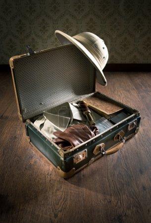 Photo pour Valise ouverte avec équipement d'exploration de style colonial, y compris casque de moelle, vieux livres et télescope en laiton . - image libre de droit
