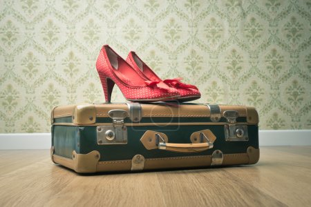 Photo for Female red dotted shoes with vintage suitcase on floor and retro wallpaper. - Royalty Free Image