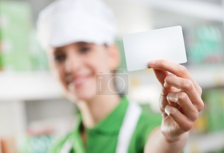 Photo for Female sales clerk holding a white card and smiling with supermarket shelf on background. - Royalty Free Image