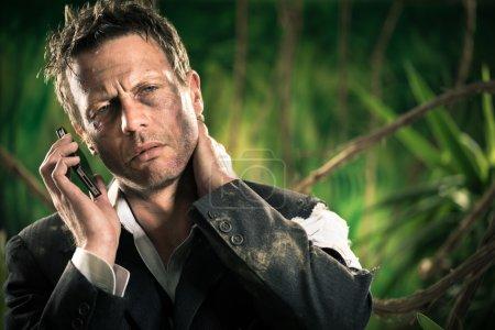 Foto de Agotado el empresario en la selva con dolor de cuello, sosteniendo teléfono móvil. - Imagen libre de derechos