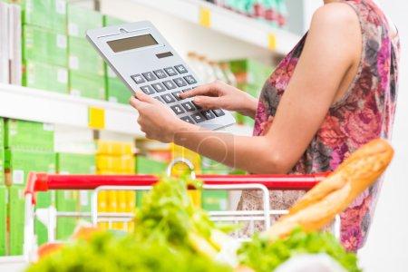 Photo pour Femme faisant des achats au supermarché avec panier et grande calculatrice vérifiant les prix . - image libre de droit