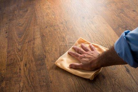 Photo pour Nettoyage manuel masculin et frottement d'un plancher de bois franc avec un chiffon en microfibre . - image libre de droit