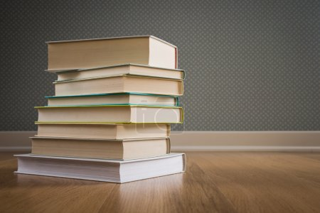 Photo for Stack of hardcover books on parquet floor with dotted wallpaper on background. - Royalty Free Image
