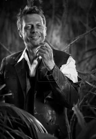Photo pour Homme d'affaires en vêtements déchirés fumant dans la jungle souriant à la caméra . - image libre de droit