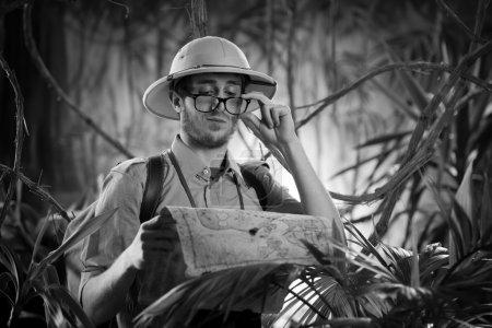 Photo pour Jeune explorateur confiant dans la jungle examinant une vieille carte et ajustant des lunettes . - image libre de droit