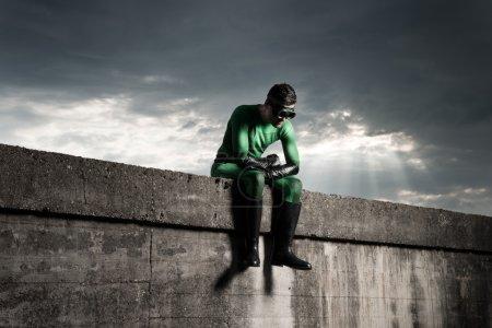 Superhero sitting on concrete wall