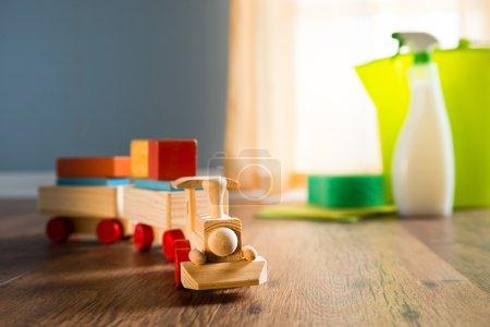 Photo pour Train jouet en bois avec nettoyage produits sur fond à côté d'une fenêtre. - image libre de droit