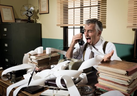 Photo for Angry vintage businessman shouting out loud at phone surrounded by adding machine tape. - Royalty Free Image