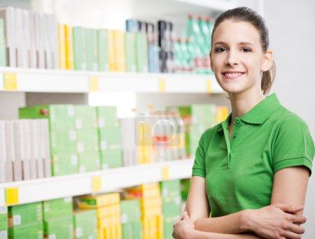 Photo pour Jeune femme attrayante avec les bras croisés au supermarché debout contre des étagères . - image libre de droit