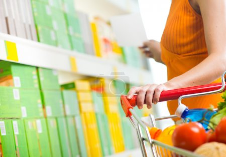 Photo for Young woman taking products from shelf at supermarket and holding a shopping cart. - Royalty Free Image