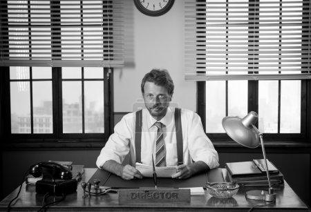 Photo pour Réalisateur vintage travaillant au bureau et regardant la caméra - image libre de droit
