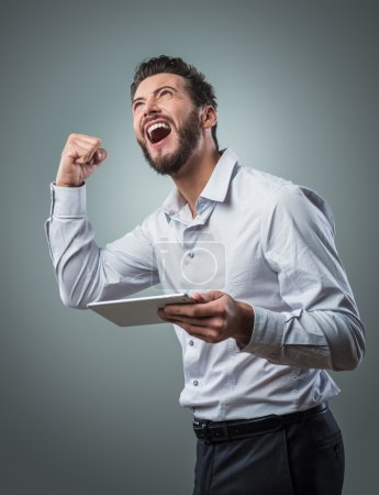 Photo for Cheerful smiling man receiving good news on tablet with fist raised - Royalty Free Image