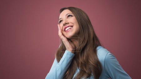 Beautiful smiling woman daydreaming