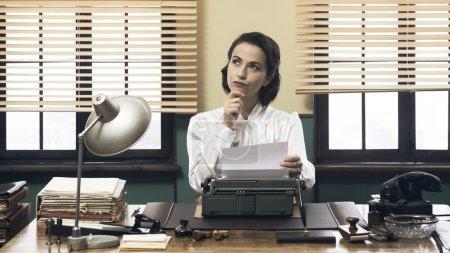 Photo pour Femme vintage pensive avec la main sur le menton, tapant sur la machine à écrire et à la recherche d'inspiration - image libre de droit