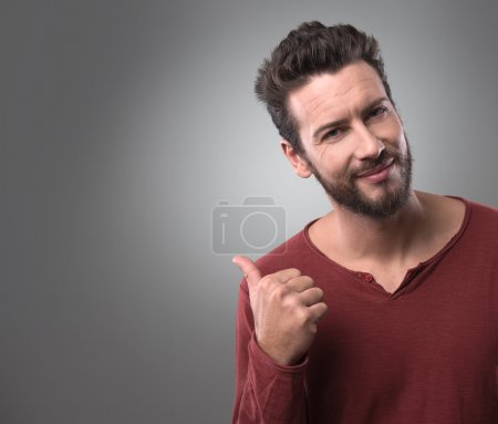 Man smiling and pointing to side