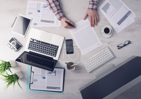 Photo pour Homme d'affaires travaillant au bureau et en signant un document, les ordinateurs et les formalités administratives tout autour, vue de dessus - image libre de droit