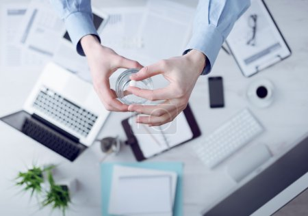 Photo for Office worker taking a pill and holding a glass of water hands close up with desktop on background, top view - Royalty Free Image