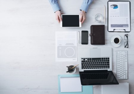 Photo for Businessman working at office desk and using a digital touch screen tablet hands detail, computer and objects on the right, top view - Royalty Free Image