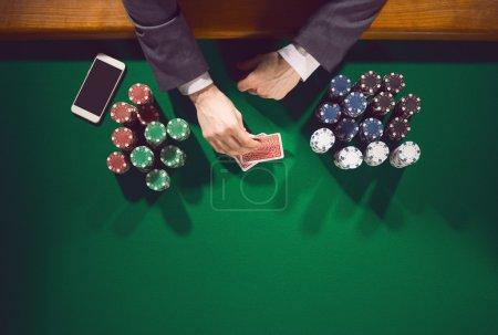 Photo pour Joueur masculin élégant de poker avec le smartphone regardant ses cartes avec des piles de jetons tout autour - image libre de droit