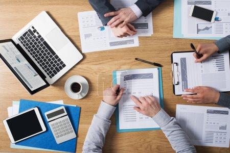 Photo pour Équipe de gens d'affaires travaillant ensemble au bureau avec l'ordinateur portatif, la tablette, la paperasse financière et les rapports, vue supérieure - image libre de droit